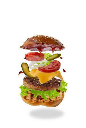 Photo pour Delicious burger with flying ingredients isolated on white background. Food levitation concept. classic burger, assembled sandwich. preparing a quick meal, fast food products. copy space - image libre de droit