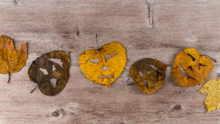 Foto de dry foliage on a wooden background. on the leaves made a scary mask. holiday of Halloween - Imagen libre de derechos