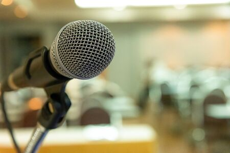 Photo pour Microphone on abstract blurred background of seminar room or speaking conference. - image libre de droit