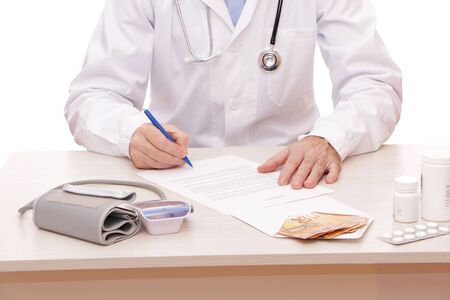 Photo pour The doctor signs a contract with the patient. On the table is a money, medical instrument a stethoscope, a medical device for measuring the pressure for listening to the lungs and heart of a patient with headphones on a white background. - image libre de droit