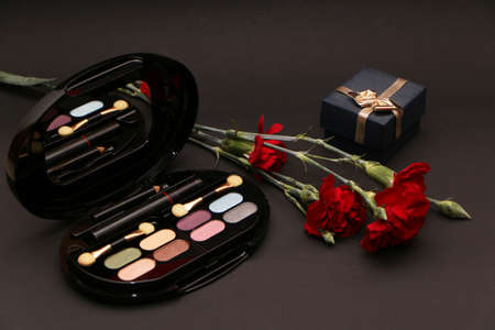 Foto de Perfume set on a wooden table is decorated with a bouquet of carnations. The background is black. Beautiful perfume bottle and female makeup on the background of a bouquet of carnations. - Imagen libre de derechos