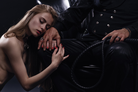 couple in bdsm action on the leather sofa