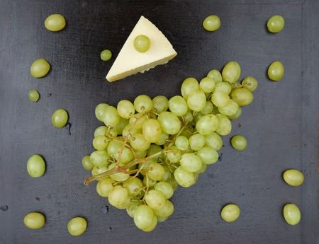 A bunch of white seedless grape and a piece of cheese on the old wooden surface. Top view. Background