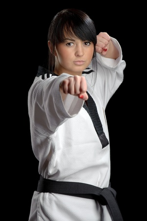 Taekwondo. Woman in a kimono isolated on the black background