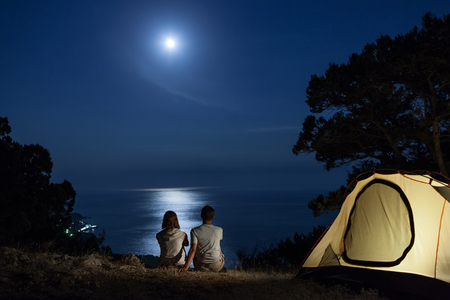 Silhouette of couple close to tent looking at moon at night above sea