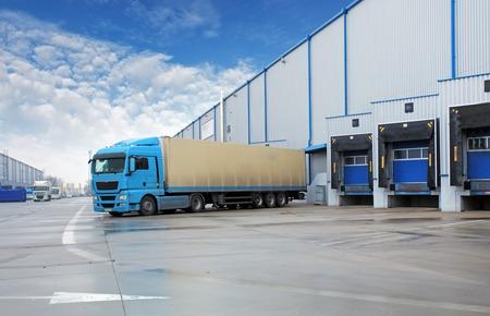 Foto de Unloading cargo truck at warehouse building - Imagen libre de derechos