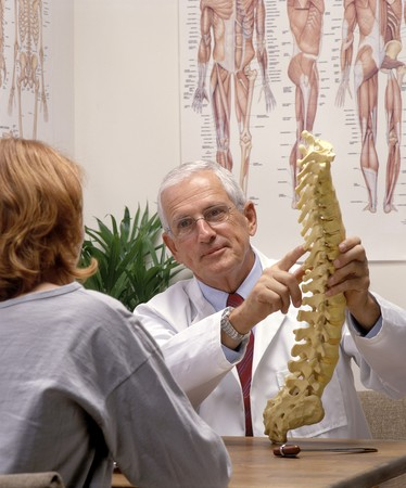 a chiropractor showing a patient a model of spine