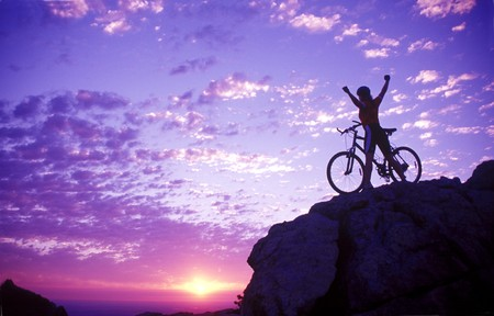 a woman on a bike holding her arms up in victory on a mountaintop