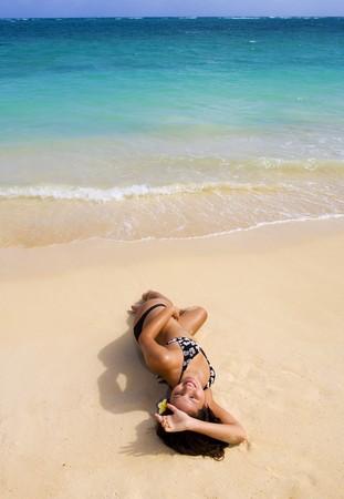 Polynesian girl in  a black bikini lying on a secluded Hawaii beach