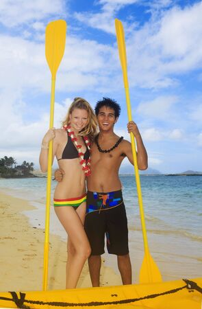 A young couple stand on the beach with their kayak and paddlesの写真素材