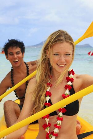 A young couple paddle a kayak in Hawaiの写真素材