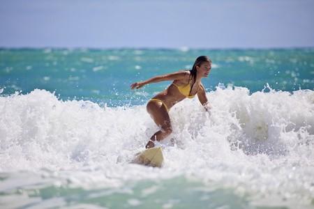 teenage girl in bikini surfing in Hawaii