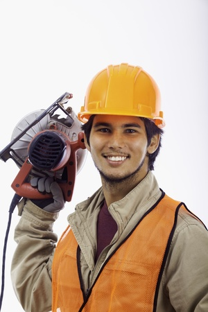 asian hardhat worker with an electric skillsaw
