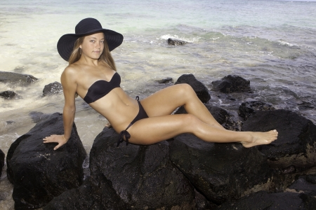 girl in bikini and hat lounging on lava rocks by the ocean