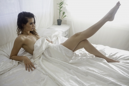 Photo for beautiful girl on a bed of white satin - Royalty Free Image