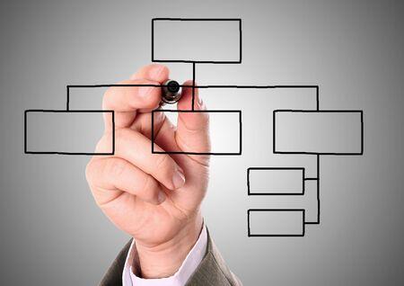 Foto de man drawing an organization chart on a gray background  - Imagen libre de derechos
