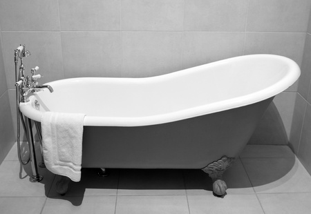 Old style bath tub with metal legs and towel, vintage style on b&w tone