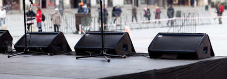 Stage monitor system, a row of stage floor monitors, three horizontal speakers on stage edge, wedges, foldbacks near the vocalists microphones, nobody. Live performance sound mixing concept