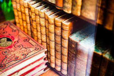 Photo pour Archaic prop hardcover books aligned on a wooden shelf closeup. Old literature reading and collecting antique shop abstract literature storage, collection concept, vivid colors, shallow depth of field - image libre de droit