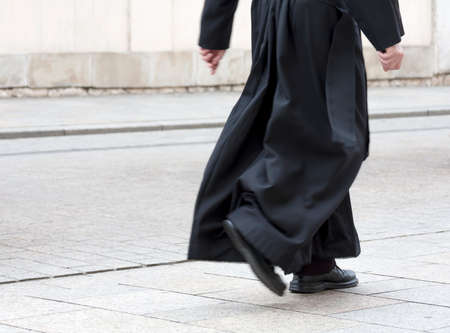 Photo pour Catholic priest in the black cassock walking on the street solo, only legs visible. Clergy, faith, christianity and calling abstract concept - image libre de droit
