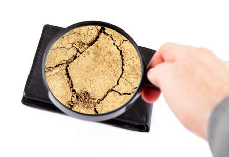 Photo for Empty wallet, no money left, drought, cracked dry earth inside. Poverty, economy financial crisis abstract concept. Personal finances dried out, no cash, trouble Hand holding a loupe, magnifying glass - Royalty Free Image