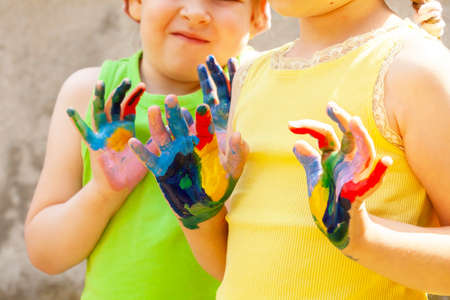 Photo pour Two happy creative school age children, colorful painted hands, kids with hands covered in multi colored paint Arts and crafts, creativity, sensory integration, kids having fun, art education concept - image libre de droit