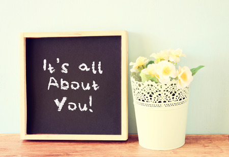 blackboard with the phrase it s all about you written on it  over wooden shelf and flowers