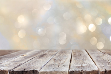 Photo pour rustic wood table in front of glitter silver and gold bright bokeh lights - image libre de droit
