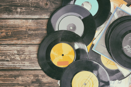 close up image of old records over wooden table , image is retro filtered .