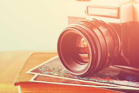 close up photo of old camera lens over wooden table. image is retro filtered. selective focus