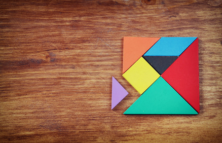 Foto de top view of a missing piece in a square tangram puzzle, over wooden table. - Imagen libre de derechos