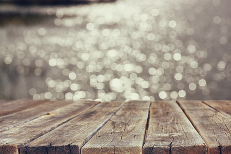 Photo pour wood board table in front of summer landscape of sparkling lake water. background is blurred - image libre de droit