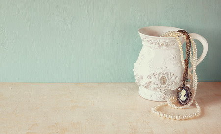 Photo pour white classic victorian vase on wooden table with a collection of romantic vintage jewelry and pearls. retro filtered image. room for text - image libre de droit