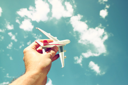 Photo pour close up photo of man hand holding toy airplane against blue sky with clouds - image libre de droit