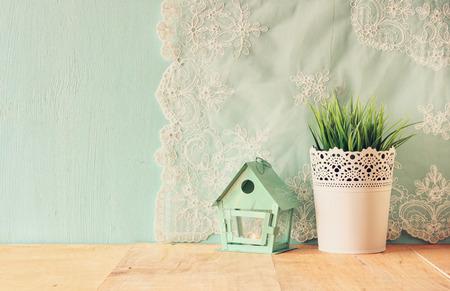 Photo pour vintage Flower pot and lantern as a bird house against mint wall and antique lace fabric - image libre de droit