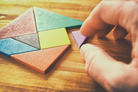Photo for a missing piece in a square tangram puzzle, over wooden table. - Royalty Free Image