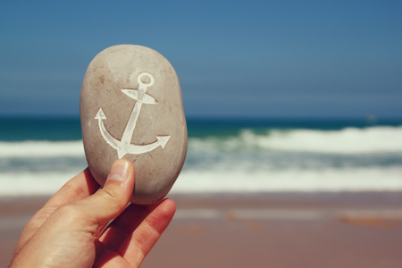 man hand holding one stone pebbles with the anchor sign  against sandy beach and sea horizon