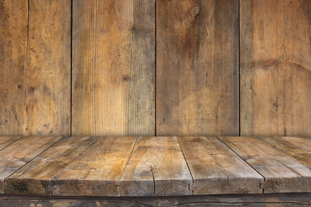 Foto de Grunge vintage wooden board table in front of old wooden background. Ready for product display montages - Imagen libre de derechos