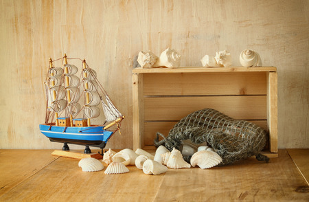 old wooden crate, boat and natural seashells on wooden table