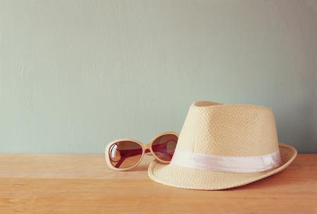 Foto de fedora hat and sunglasses over wooden table. relaxation or vacation concept - Imagen libre de derechos