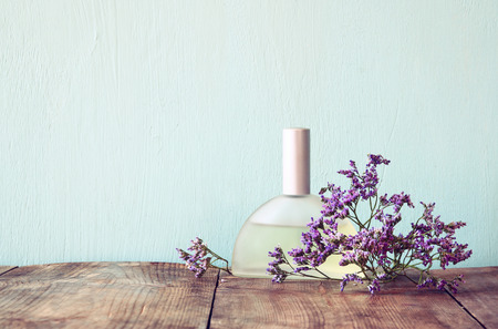 fresh vintage perfume bottle next to aromatic flowers on wooden table. retro filtered image