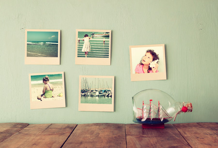instant photos hang over wooden textured background next to decorative boat in the bottle. retro filtered image