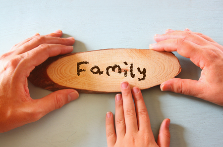 family hands holding sign with the word familly