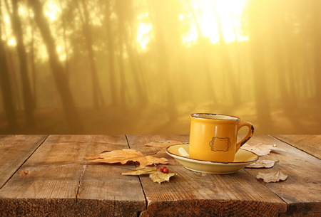 front image of coffee cup over wooden table and autumn leaves in front of autumnal sunset backgroundの写真素材
