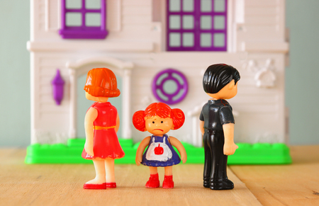 Photo for concept image of parent busy or angry and child in the middle in front of. little plastic toy dolls male, female, child, selective focus. - Royalty Free Image