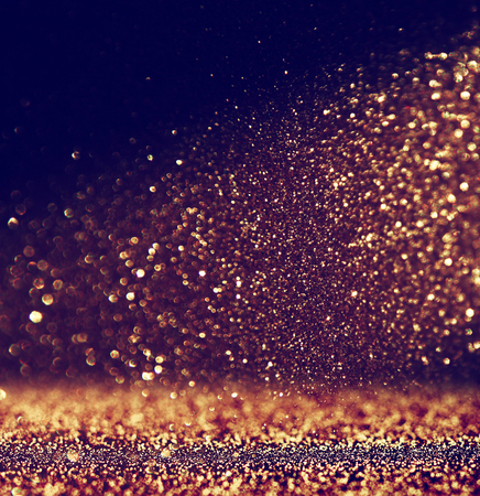 glitter vintage lights background. gold and black. defocused