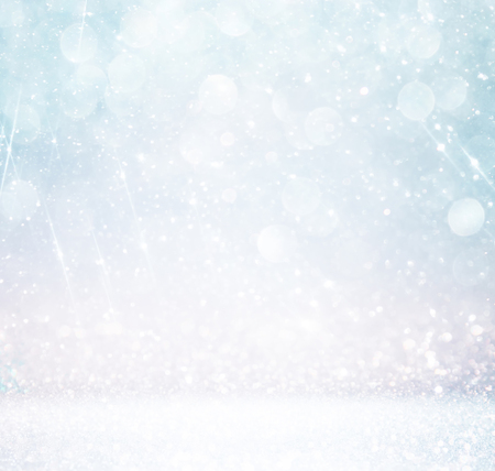 bokeh lights background with multi layers and colors of white silver and blue with snowflakes overlay