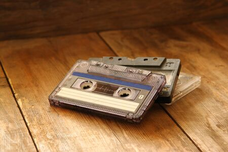 selective focus of Cassette tape over wooden table. image is instagram style filtered.