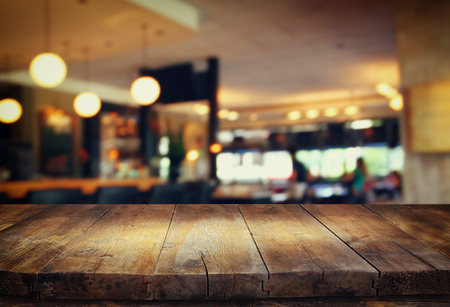 image of wooden table in front of abstract blurred background of restaurant lightsの写真素材