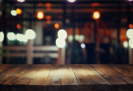 Photo for image of wooden table in front of abstract blurred background of restaurant lights - Royalty Free Image